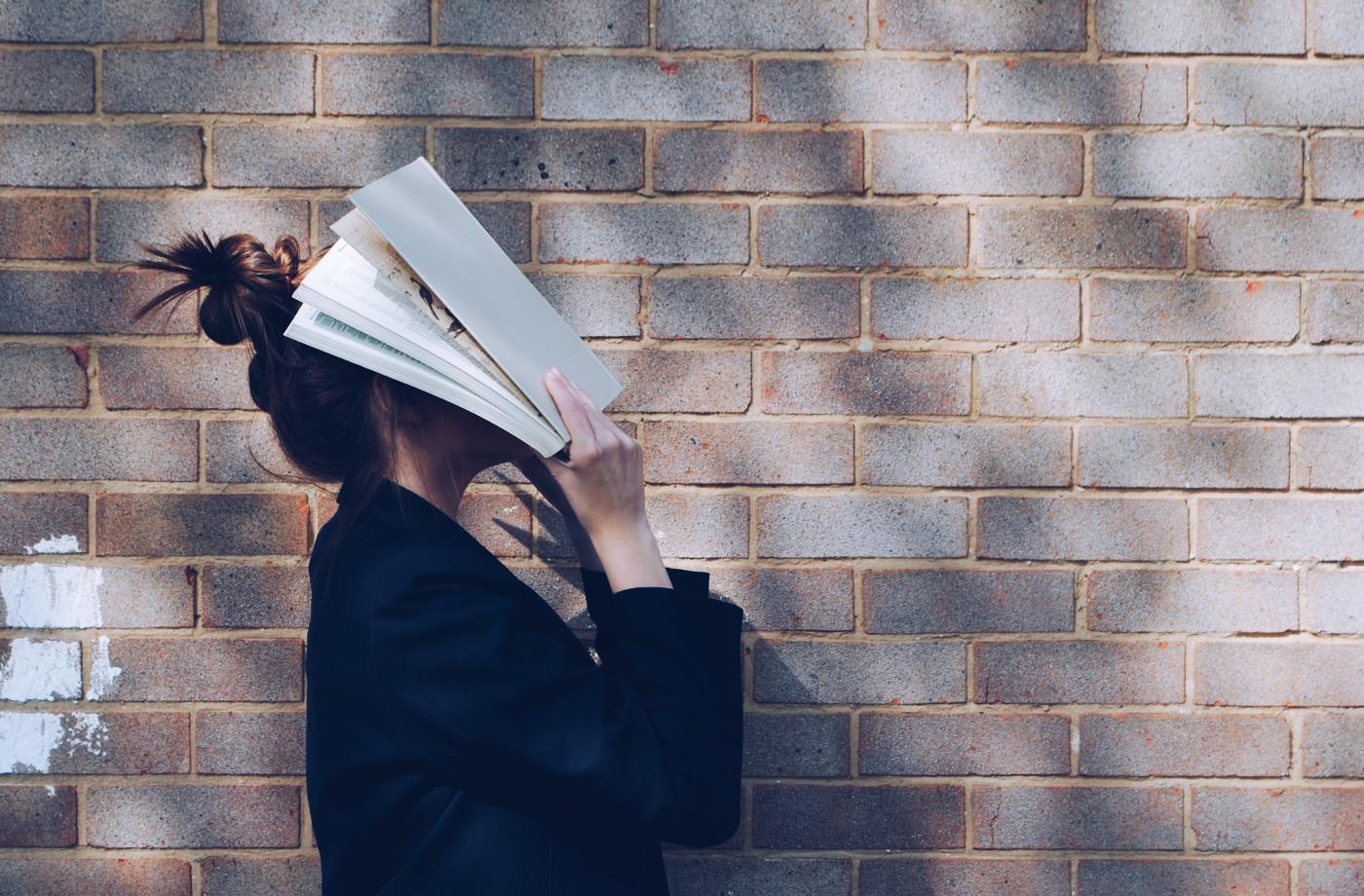 Der Mensch und sein Weib - Eine Frau steht seitlich von einer Backsteinmauer und hat sich mit beiden Händen ein großes Buch auf das Gesicht gelegt.