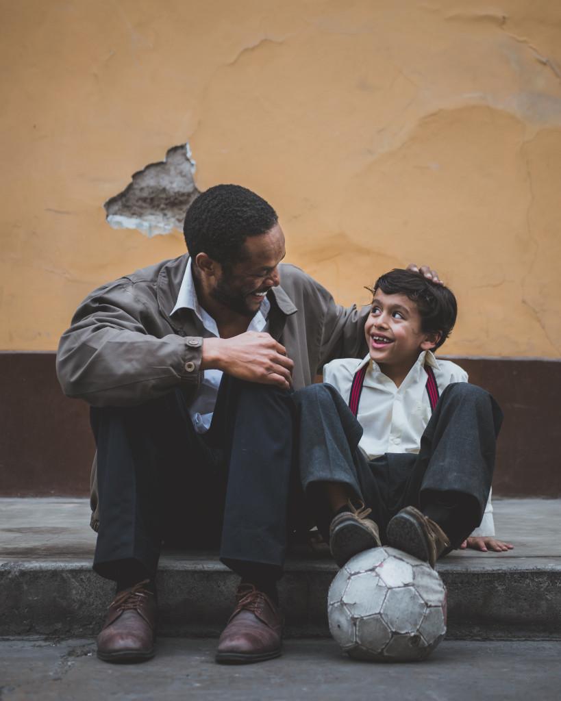 Männer sind Söhne: Ein Mann und ein kleiner Junge mit einem Fußball sitzen nebeneinander auf einer niedrigen Steinstufe und lächeln sich an.
